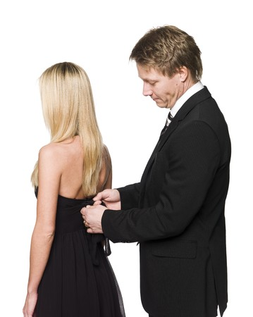 get dressed: man helping woman to get dressed Stock Photo