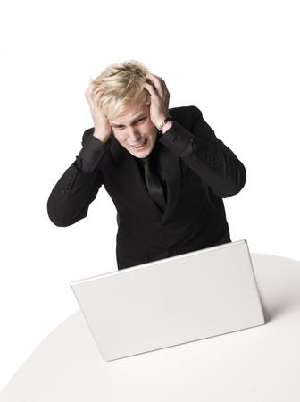 saddened: Man looking on a computer Stock Photo