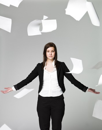 gray backgrund: Office girl with a lots of papers flying around Stock Photo