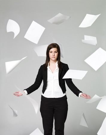Office girl with a lots of papers flying around Stock Photo