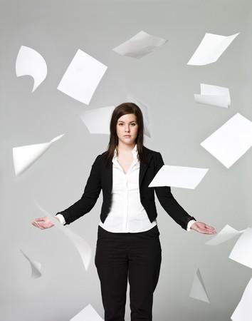 papeles oficina: Oficina de una chica con un mont�n de papeles volando por ah� Foto de archivo