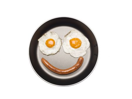 breakfast smiley face: Saucepan with eggs and sausage