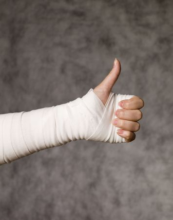 arms up: Person with bandage doing thumbs up