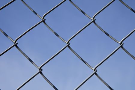 hedging: Fence as a pattern towards blue sky Stock Photo