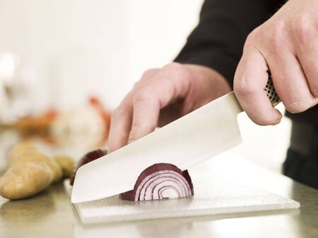 Cutting onion with a knife photo