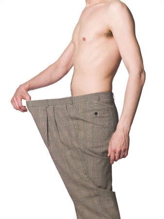 Man with oversized trousers towards white background photo