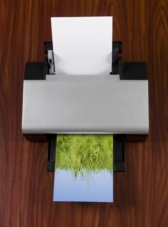 short focal depth: Printer prints an image with green grass towards blue sky