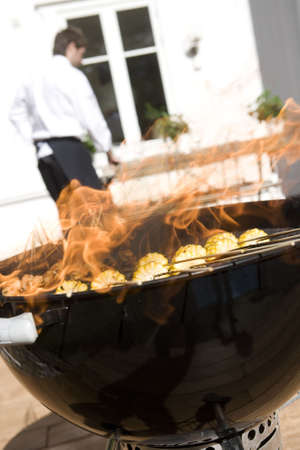 unrecognizable: Outdoor barbecue with corn on the grill