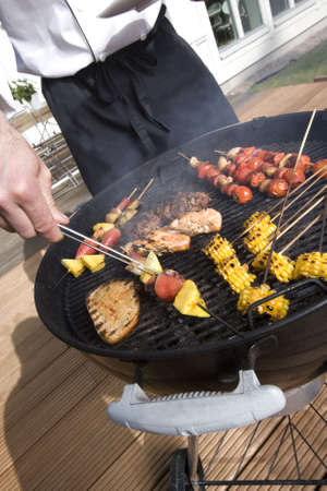 grill tongs sausage: Man at the grill outdoor