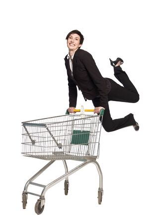 Jumping woman with a shopping cart Stock Photo