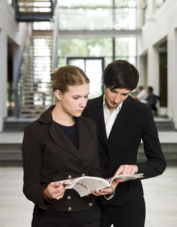 Two women reading a magazine while standing in an office building photo