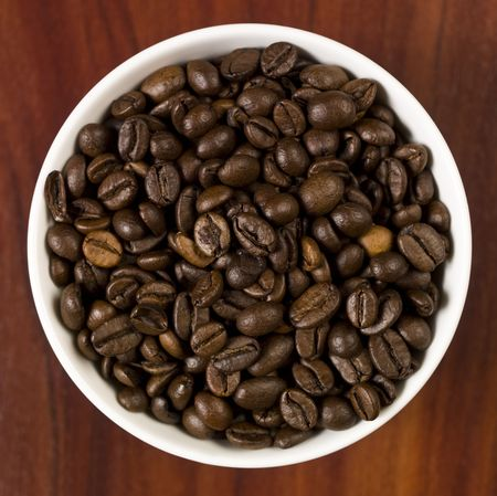 High angle view of coffee beans in a cup with a wooden background. photo