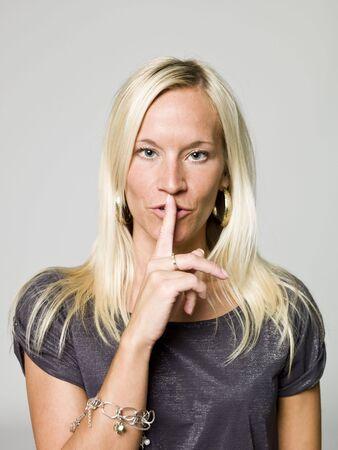 shushing: Portrait of a woman shushing Stock Photo