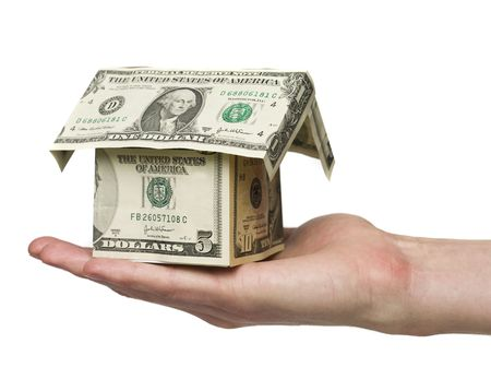 house prices: Man holding a small house built out of dollar bills