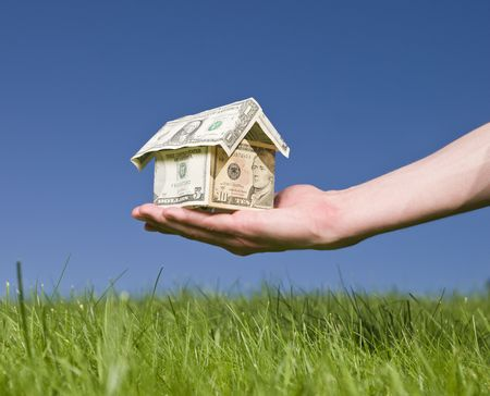 Man holding a dollar house outside photo