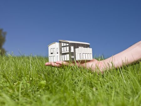 Man holding a miniature house outside in the sun. Stock Photo - 5531484