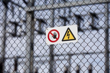 Warning signs on a fence with short focal depth.