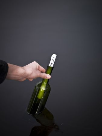 Hand picking up a bottle with a message in it. photo