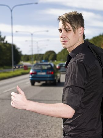 A young man hitchiking on the road photo