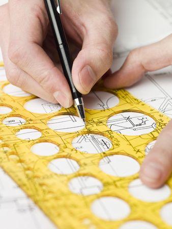 Male architect working on a bluprint, close up on hand and bluprint. photo