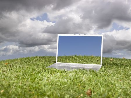 Laptop outdoors on a green field with a moody sky background Stock Photo - 5624552