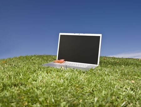 Laptop outdoors on a green field with a blue sky background photo