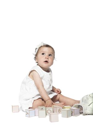 Girl playing with alphabet blocks isolated on a white background photo