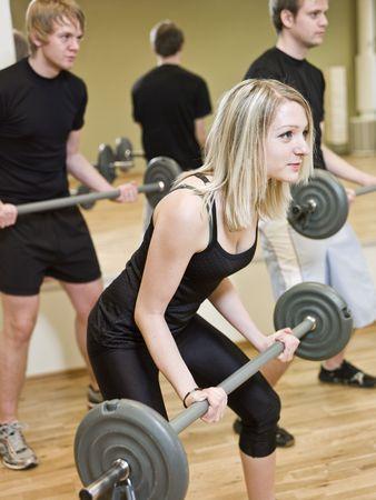 pesas: Chica de levantamiento de pesas en el gimnasio