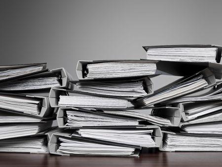 Überwältigende Anzahl von Dateien, die auf einem Schreibtisch gestapelt  Standard-Bild