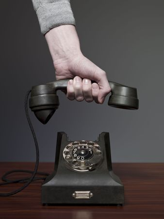 inddor: Man answering retro phone against a grey background