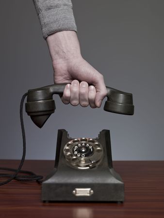 Hand picking up retro phone against a grey background photo