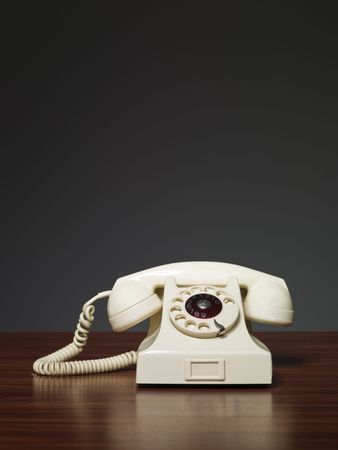 Plastic retro phone on a desk against a grey background Stock Photo