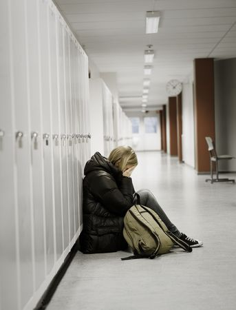 Young woman crying by the lockers at school