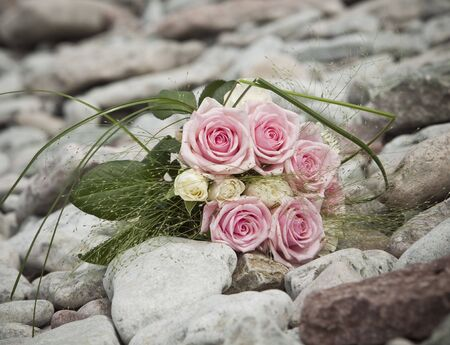 Bouquet of pink and white roses lying on rocks photo
