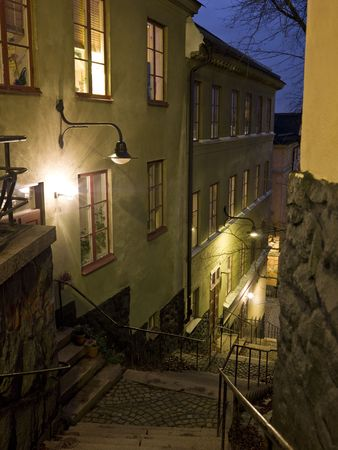 Alley with stairs at night in a city photo