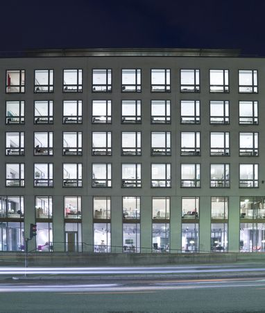 Office building with several windows at night Stock Photo