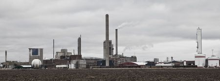 Industrial buildings behind a field on a cloudy day Stock Photo - 6090911