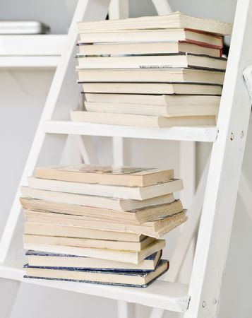 bibliomania: Pile of books on a ladder Stock Photo