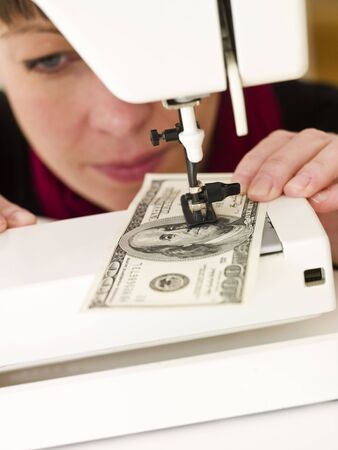 Woman holding with Hundred dollar bank note in a sewing machine Stock Photo - 6827821