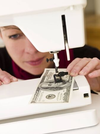 Woman sewing a hundred dollar banknote Stock Photo - 6827859