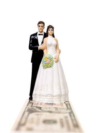 Wedding couple standing on a Dollar bank note isolated on white background photo
