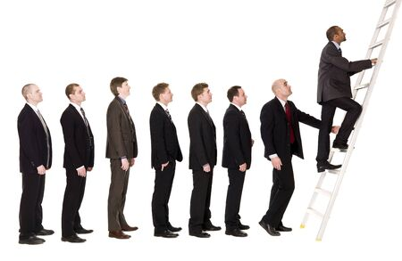 Group of men standing in line to climb a ladder photo