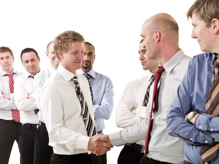 Businessmen shaking hands standing in  group of people photo