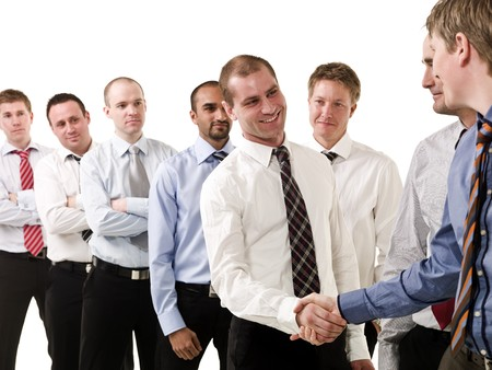 Businessmen shaking hands standing in a group of people photo