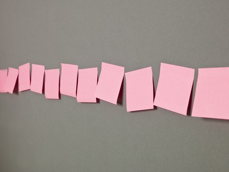 Row of Pink Adhesive Notes on grey background Stock Photo - 7039520