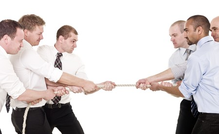 pull out: Businessmen in a tug-of-war isolated on white background Stock Photo