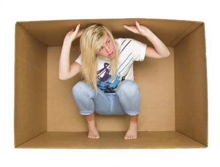 claustrophobia: Young woman inside a Cardboard Box isolated on white Archivio Fotografico