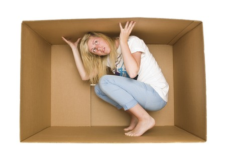 claustrophobic: Young Woman inside a Cardboard Box isolated on white Background