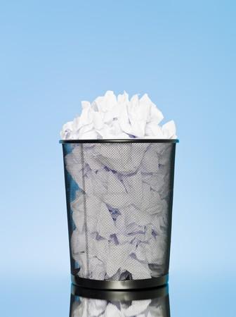 Full wastebasket on blue background photo