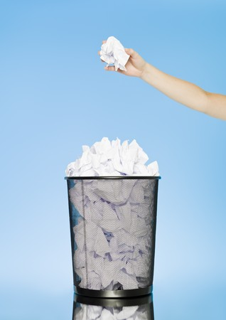 wastebasket: Human trowing a paper to a wastebasket on blue background Stock Photo